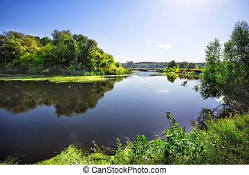 Sunny day on the river with green trees on the shore