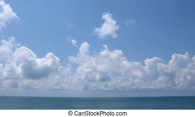 Sunny day on the sea, clouds move on the sky.
