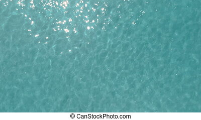 Sunny day top view of crystal clear water, looped background, natural texture