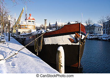Sunny harbour with iron ship in winter snow