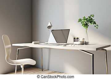Sunny home office work place with light wooden furniture, modern laptop and coffee mug
