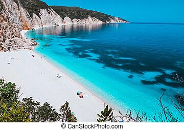 Sunny idyllic Fteri beach lagoon with limestone rocky coastline, Kefalonia, Greece. Tourists relax under umbrella near clear blue emerald turquoise sea water with dark pattern on bottom