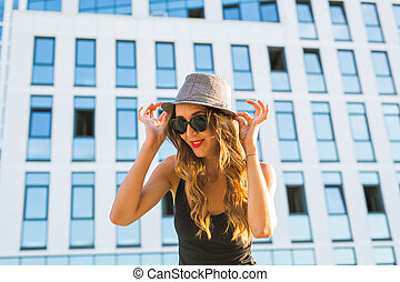 Sunny lifestyle close-up fashion portrait of young stylish hipster woman walking on the street, wearing trendy outfit and hat.