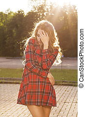 Sunny lifestyle portrait of young stylish model walking in the park and wearing trendy dress