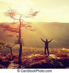 Sunny morning. Happy hiker with hands in the air stand on...