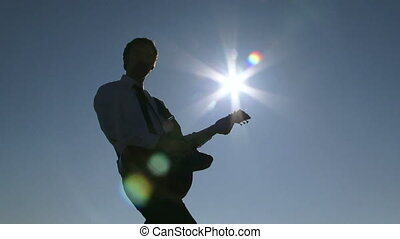 Sunny musician - Well-dressed man playing guitar in the...