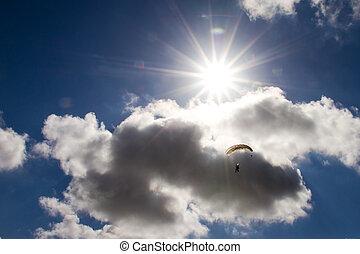 Parachute backlit against a sunny cloudy sky