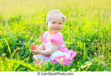 Sunny photo smiling child sitting on the grass in summer day