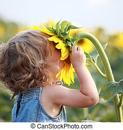 Sunny - Cute child with sunflower in summer field