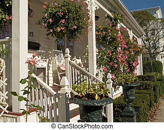 This is a shot of a white porch decorated nicely with some hanging flower baskets.