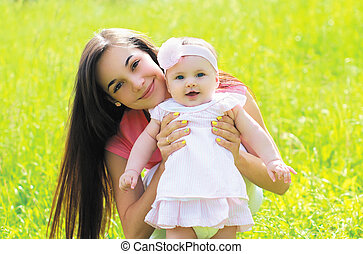 Sunny portrait of happy young mother with baby on the grass in summer warm day