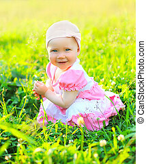 Sunny portrait of smiling child sitting on the grass in summer day