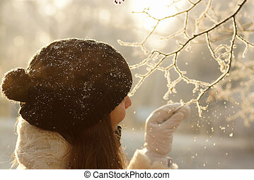 Sunny portrait of young woman in black hat with pompom and white mittens touching snowy icy tree branch in winter forest