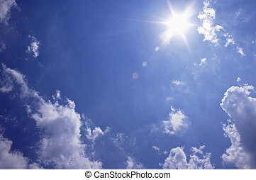 Sun and clouds against a blue sky at high noon