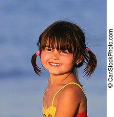 Face of a young little girl smiling, wearing a red and yellow swimsuit and with her hair in pigtails. Summer scene.