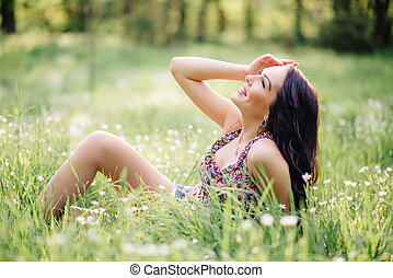 sunny summer day, a beautiful young woman lying on the grass