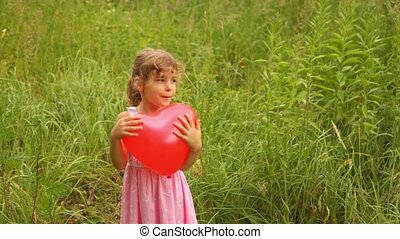 girl is throwing up an inflatable heart merrily - sunny...