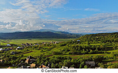 Sunny summer day and small village in montain in a blue sky