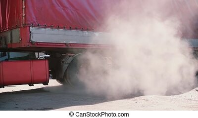 A red lorry turning right. Cloud of dust in the air. - Sunny...