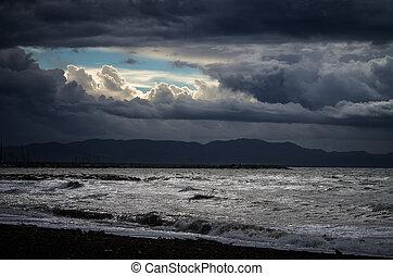 Sunny window between stormy clouds over mediterranean sea