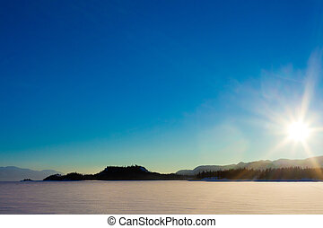 Sunny Winterday - Sun and blue sky over frozen lake.