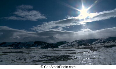 Clouds move fast while the sun shines onto an icy cold landscape.