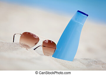 sunprotection summer holiday sunglasses and cream in sand macro