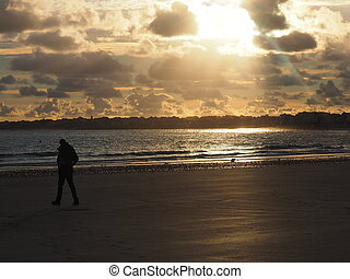 sunraise at the beach of st. Malo - lonley man on the beach...