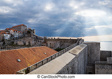 Sunrays shining out of the dramatic cloudscape over walkway up to the fortress of Durbrovnik, Croatia