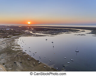 Sunrise aerial seascape, in Ria Formosa wetlands natural...