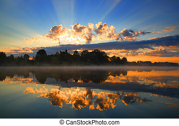 sunrise and reflection in river - sunrise with sunbeams and...