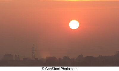 Sunrise at city with high-voltage power transmission line...