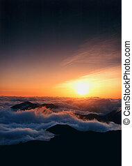 Sunrise at the top of Mt. Haleakala in Maui, Hawaii, with a sea of clouds that look like waves