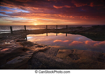 The Ivo Rowe pool is a natural rockpool fed by the ocean in high tide. It's eroded rocks and weathered timber and chaim fence are intresting features. The stunning sunrise of reds and oranges in the sky colours its tranquil waters and highlights the rocks with tinges of colour also