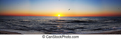 Panorama shot of sun rising over the sea