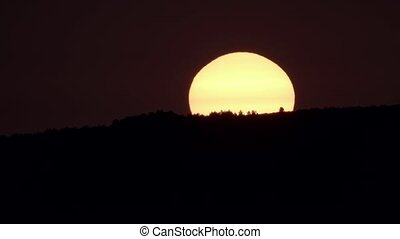 Sunrise behind dark hill and huge orange sun - Long shot...
