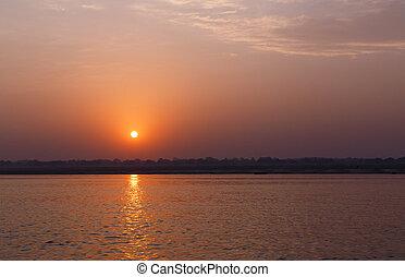 sunrise behind Ganga river in Varanasi, India