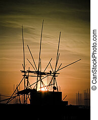 Sunrise behind the bamboo structure of a building under construction