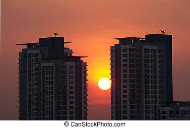 Sunrise between building at Bangkok, Thailand.