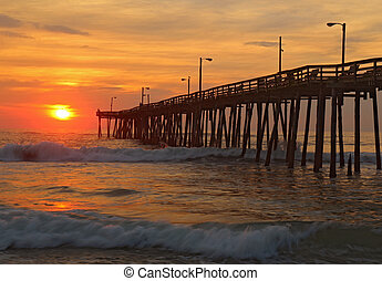 Sunrise by a fishing pier in North Carolina - The rising sun...