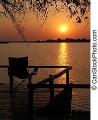 Sunrise dock - 3 - A single chair facing the sunrise on a...