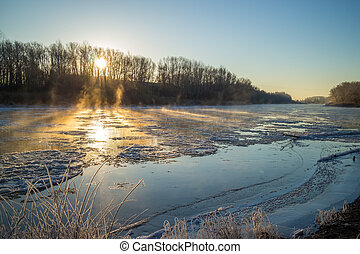 Sunrise on the banks of the freezing and foggy river