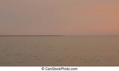 Sunrise from fishing pier. Shows calm water and shore with...