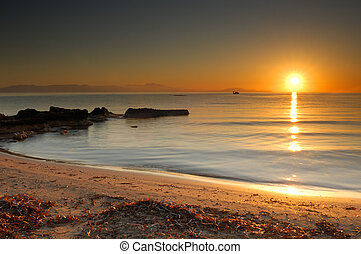 Image shows the sun rising over a mediterranean beach