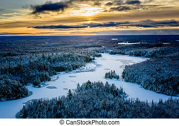 Sunrise in early winter over a lake and forest
