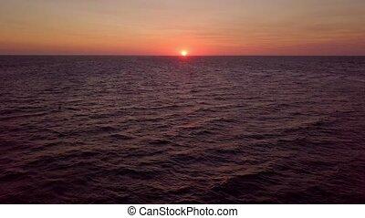 Sunrise in ocean - Aerial panoramic view of bright red sun...