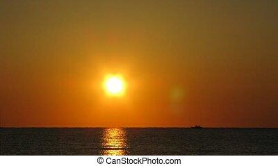 Sunrise in sea, on sea ship floats.