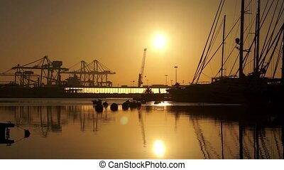 sunrise in the harbor of Valencia, the sun rises between...