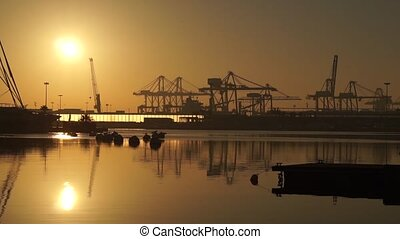 sunrise in the harbor of Valencia, the sun rises between docked sailboats and cargo port cranes