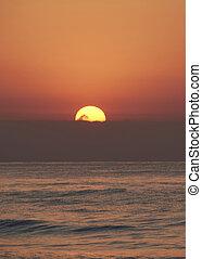 Sunrise in the ocean, the sun appears